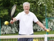 Portrait of senior tennis coach standing at net and serve the ball on tennis court while playing match.