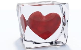 Red heart frozen in ice cube isolated on white