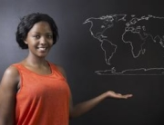 Confident beautiful South African or African American woman teacher or student with chalk geography world map on blackboard background
